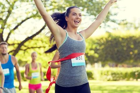 fitness, sport, overwinning, succes en een gezonde levensstijl concept - tevreden vrouw winnende race komend eerste rood lint afwerking over groep sporters loopt marathon met badge nummers buiten