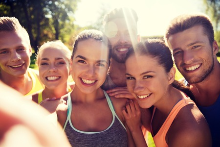 fitness, deporte, la amistad, la tecnología y el concepto de estilo de vida saludable - grupo de amigos adolescentes felices que toman selfie con el teléfono inteligente al aire libre Foto de archivo