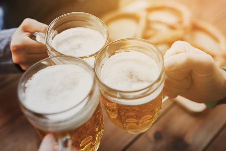 people, leisure and drinks concept - close up of male hands clinking beer mugs at bar or pub Foto de archivo