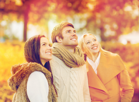 summer, holidays, vacation, happy people concept - group of friends having fun in autumn park