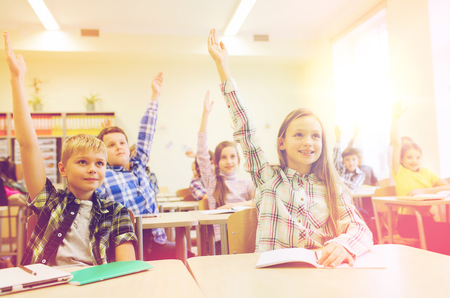 elementary school: education, elementary school, learning and people concept - group of school kids with notebooks sitting in classroom and raising hands Stock Photo