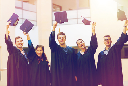 hi hat: education, graduation and people concept - group of smiling students in gowns waving mortarboards outdoors