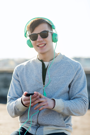 technology, lifestyle and people concept - smiling young man or teenage boy in headphones with smartphone listening to music outdoors Stock Photo