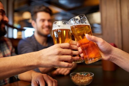 bachelor: people, men, leisure, friendship and celebration concept - happy male friends drinking beer and clinking glasses at bar or pub