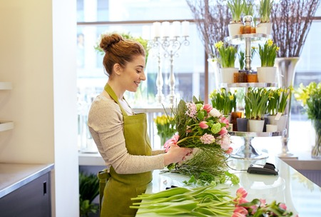 floristry: people, business, sale and floristry concept - happy smiling florist woman making bunch at flower shop
