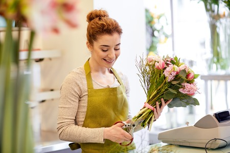 floristry: people, business, sale and floristry concept - happy smiling florist woman making bunch and cropping stems by scissors at flower shop