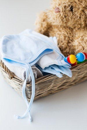 babyhood: babyhood, motherhood, clothing and object concept - close up of baby clothes and toys for newborn boy in basket Stock Photo