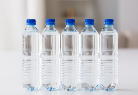 food storage: recycling, healthy eating, industry, packing and food storage concept - close up of plastic bottles with pure drinking water on table Stock Photo