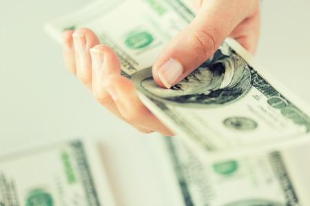 ビジネス、金融、銀行と人々 のコンセプト - 節約をドルのお金を数える私たち女性の手のクローズ アップ