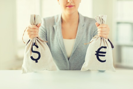 business, finance, saving, banking and people concept - close up of woman hands holding dollar and euro money bags Stock Photo