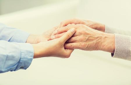 人、時代、家族、ケアとサポートのコンセプト - シニアと若い女性が手をつないでのクローズ アップ