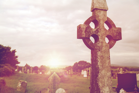 ancient ireland celtic cross: ancient monument and burial concept - old grave cross, headstones and ruins on celtic cemetery graveyard in ireland
