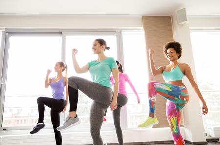 adentro y afuera: fitness, deporte, entrenamiento, ejercicio y concepto de la gente - grupo de mujeres felices que se resuelve y que levanta las piernas en el gimnasio de la pierna Foto de archivo