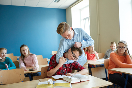 mockery: education, bullying, violence, aggression and people concept - student boy suffering of classmate mockery Stock Photo