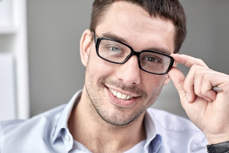 face work: business, people and work concept - portrait of smiling businessman in eyeglasses face in office Stock Photo