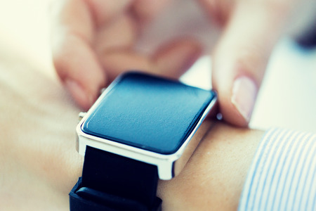 business, technology and people concept - close up of woman hands setting smart watch