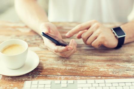 Wirtschaft, Technologie und Menschen Konzept - Nahaufnahme Smartphone der männlichen Hand hält und trägt Uhr mit Kaffee und Tastatur auf Holztisch