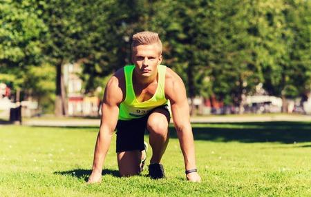 sportsman: fitness, deporte, maratón y el concepto de estilo de vida saludable - deportista joven con número de placa en Inicio de carrera al aire libre