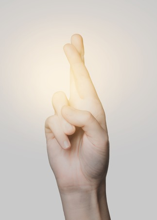 body parts: gesture and body parts concept - close up of hand showing two cross fingers Stock Photo