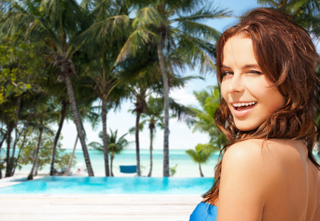 travel, tourism, summer vacation and people concept - happy beautiful woman over tropical beach or resort hotel swimming pool background Stock Photo