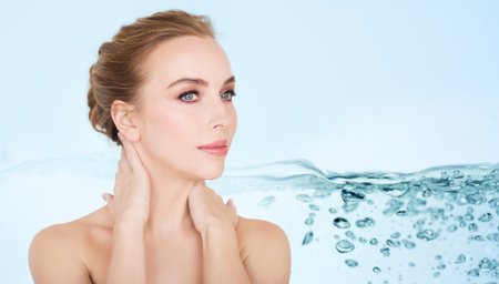 white face: beauty, people, moisturizing and skincare concept - beautiful young woman face and hands over white background
