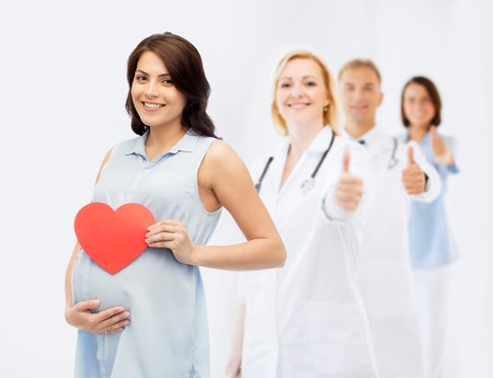 pregnancy, healthcare, medicine, people and expectation concept - happy pregnant woman with red heart shape touching her belly over group of doctors or obstetricians showing thumbs up background