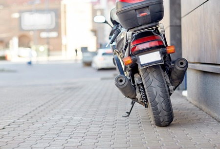 parked: transport, vehicle and travel concept - close up of motorcycle or bike parked on city street pavement