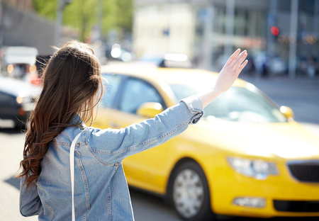 catching taxi: gesture, transportation, travel, tourism and people concept - young woman or teenage girl catching taxi on city street or hitch-hiking