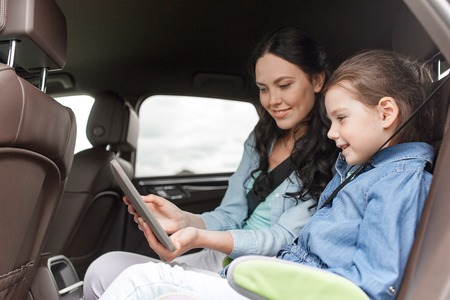 family, transport, road trip, travel and people concept - happy woman and little daughter with tablet pc computer driving in car Stockfoto