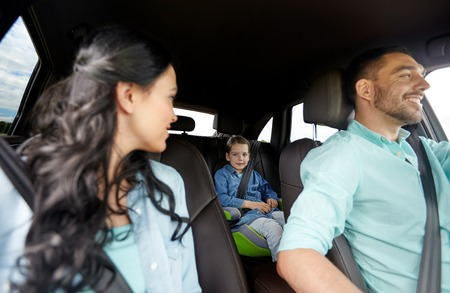 family, transport, safety, road trip and people concept - happy man and woman with little child driving in car Stock Photo - 64174320