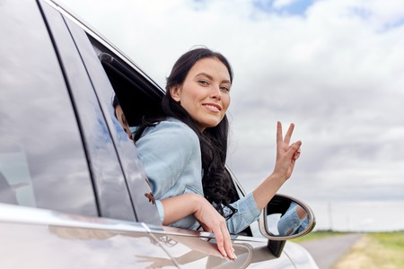 summer sign: summer vacation, holidays, travel, road trip and people concept - happy young woman driving in car and showing peace sign Stock Photo