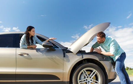 road trip, transport, travel and people concept - family couple with open hood of broken car at countryside Stock Photo
