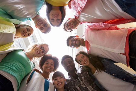 education, school, friendship and unity people concept - group of happy international students standing in circle Stock Photo
