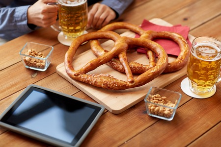 people, leisure, technology and drinks concept - close up of man drinking beer with pretzels, peanuts and tablet pc computer on table at bar or pub Stock Photo