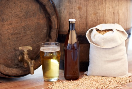 alehouse: brewery, drinks and alcohol concept - close up of old beer barrel, glass, bottle and bag with malt on wooden table
