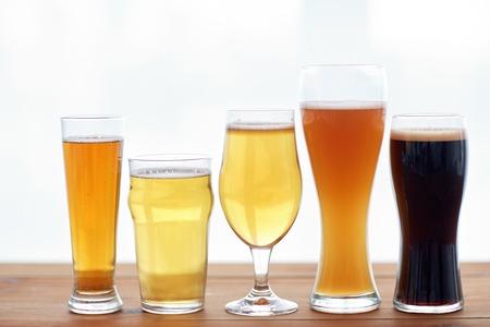 cerveza negra: fábrica de cerveza, bebidas y alcohol concepto - cerca de cervezas diferentes de gafas en la tabla Foto de archivo