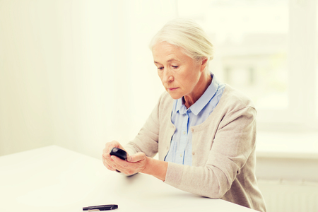 health care and medicine: medicine, age, diabetes, health care and people concept - senior woman with glucometer checking blood sugar level at home