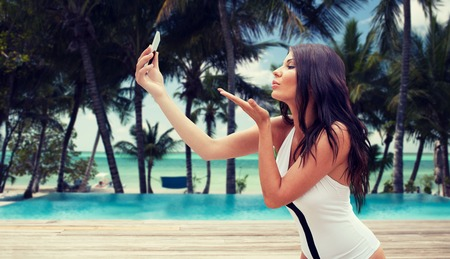 summer, travel, technology and people concept - sexy young woman taking selfie with smartphone and sending blow kiss over tropical beach with palms and swimming pool background