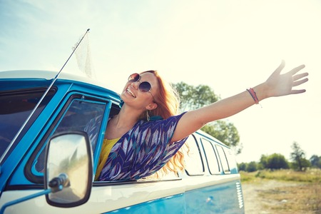 mujer hippie: summer holidays, road trip, vacation, travel and people concept - smiling young hippie woman driving minivan car and waving hand Foto de archivo