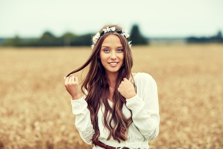mujer hippie: nature, summer, youth culture and people concept - smiling young hippie woman wearing flower wreath on cereal field Foto de archivo
