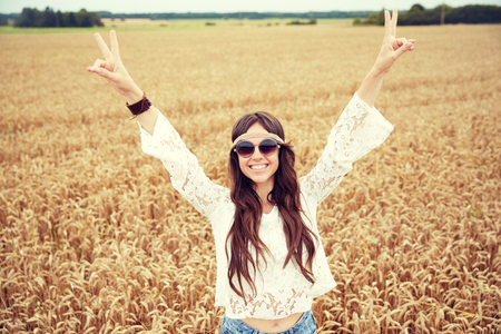 groovy: nature, summer, youth culture and people concept - smiling young hippie woman in sunglasses on cereal field Stock Photo