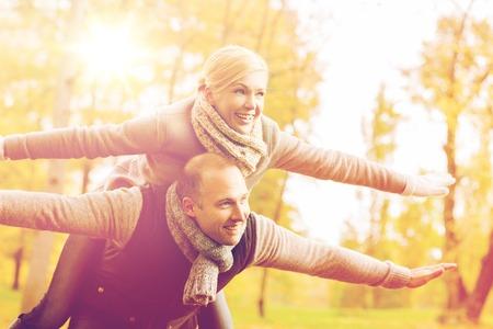 Liefde, relatie, familie en mensen concept - lachende paar plezier in de herfst park Stockfoto - 64213958