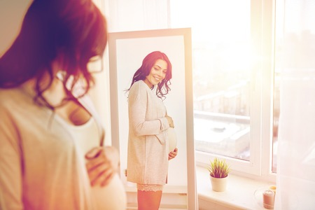 pregnancy, motherhood, people and expectation concept - happy pregnant woman looking to mirror at home Stock Photo