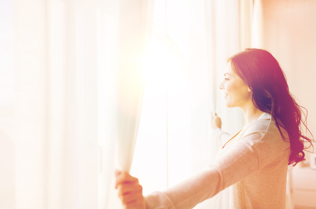 people and hope concept - close up of happy woman opening window curtains Stock Photo