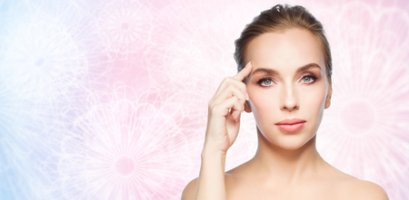beauty, people and plastic surgery concept - beautiful young woman pointing finger at her forehead over pink patterned background