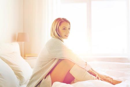 mujer en la cama: descansar, dormir, la comodidad y las personas concepto - mujer joven feliz sentado en la cama en el dormitorio en casa Foto de archivo