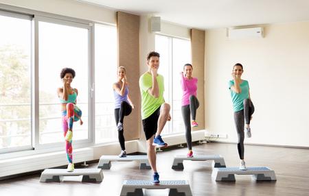 gimnasia aerobica: fitness, deporte, ejercicio, aeróbicos y concepto de la gente - grupo de gente sonriente que se resuelven en plataformas de paso en el gimnasio