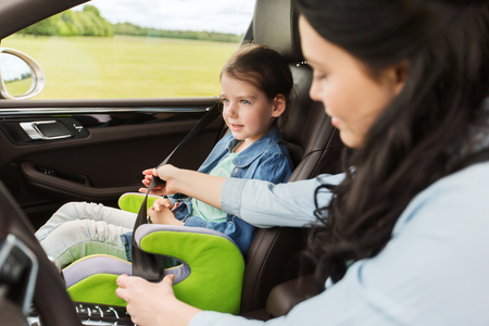 road safety: family, transport, road trip and people concept - happy woman fastening child with safety seat belt in car Stock Photo