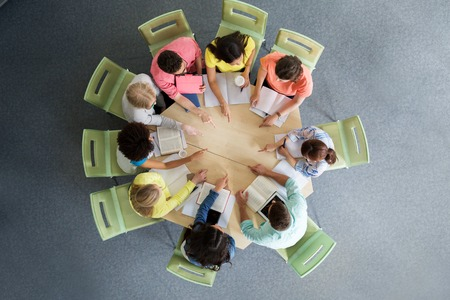 round: education, school, teamwork, gesture and people concept - group of international students with books sitting and pointing finger to center of table from top Stock Photo