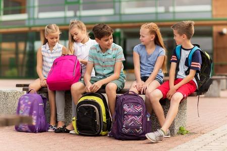 기본 교육, 우정, 어린 시절, 통신 및 사람들이 개념 - 벤치에 앉아 야외 얘기 배낭을 행복 초등학교 학생들의 그룹 스톡 콘텐츠 - 64214051